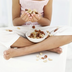 Young Girl (8-9) Holding Nuts in Her Hands and a Bowl of Nuts on Her Lap --- Image by © Royalty-Free/Corbis